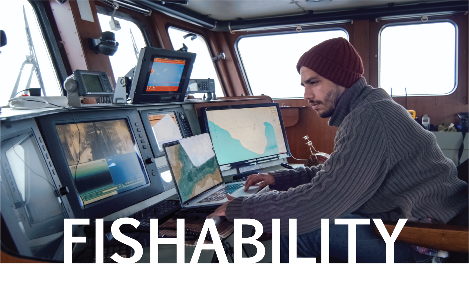 Man sitting in captains seat on commercial fishing boat with text fishability over image