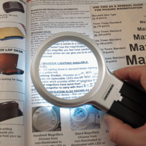 Handheld magnifier with LED light enlarging text on paper