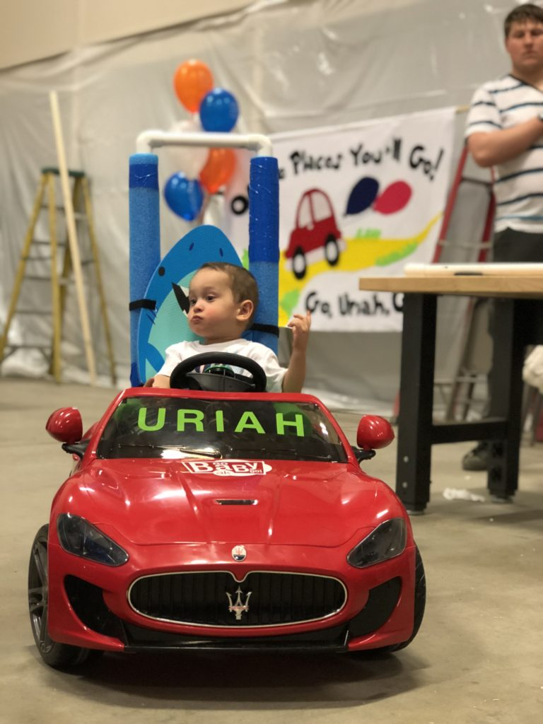 young boy in ride on car