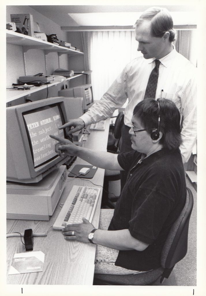 man standing next to man who is using a computer