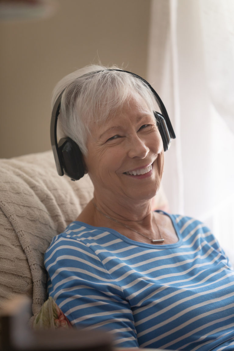 Happy mature Female Smiling while Listening to headphones